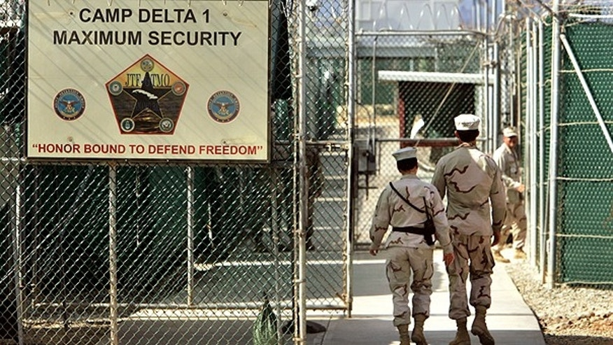 In this file photo from June 27, 2006, reviewed by a U.S. Department of Defense official, U.S. military guards walk within Camp Delta military-run prison, at the Guantanamo Bay U.S. Naval Base, Cuba.