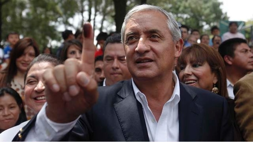 Guatemala's presidential candidate of the Patriotic Party Otto Perez Molina, shows his ink-stained thumb after casting his vote at a polling during the country's presidential elections in Guatemala City, Sunday, Sept. 11, 2011. (AP Photo/Moises Castillo)