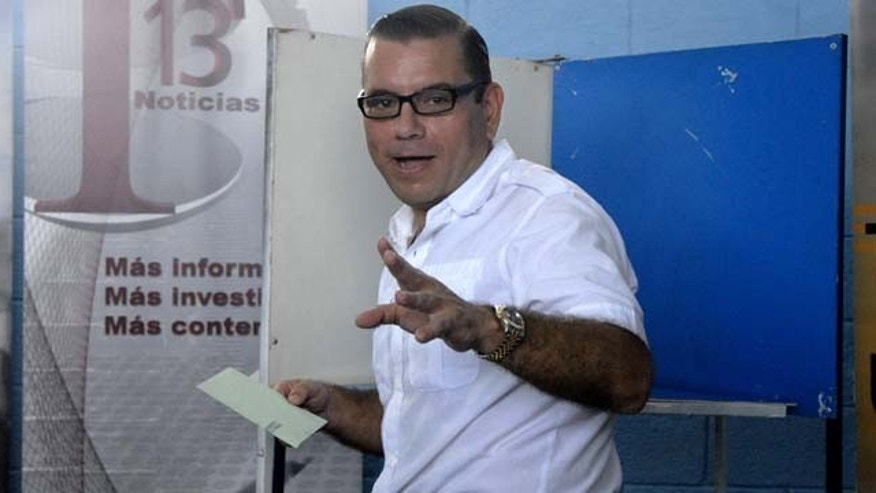 Manuel Baldizon, presidential candidate of Guatemala's Democratic Freedom Revival Party, gestures after marking his ballot in a voting booth during the country's general elections in Peten, Guatemala, Sunday Sept. 11, 2011. Baldizon, a tycoon-turned-political populist is the closest challenger of leading presidential candidate Otto Perez Molina in a field of 10 candidates, according to polls. (AP Photo/Alex Cruz)