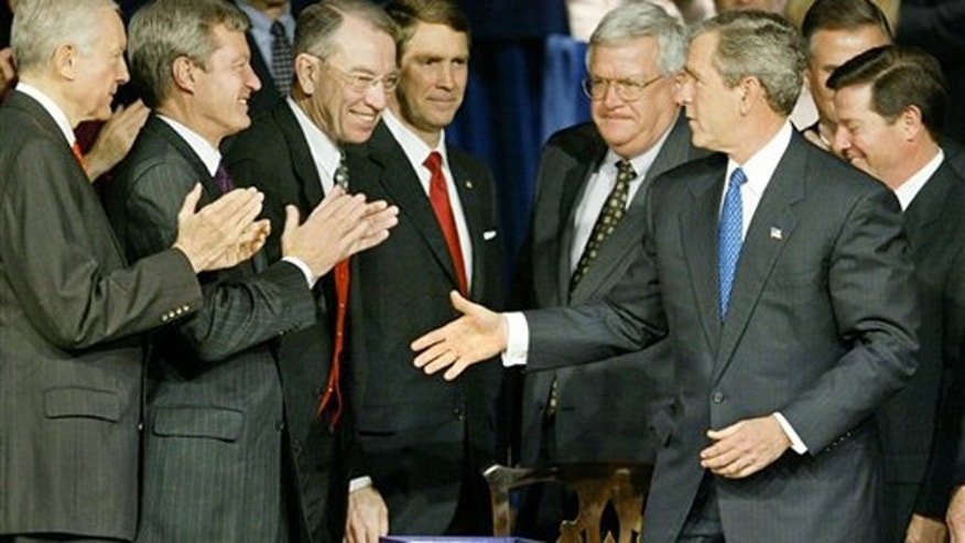 In this Dec. 8, 2003, file photo then-President George W. Bush greets applauding congressional leaders as he signs into law the Medicare prescription drug benefit in Washington.
