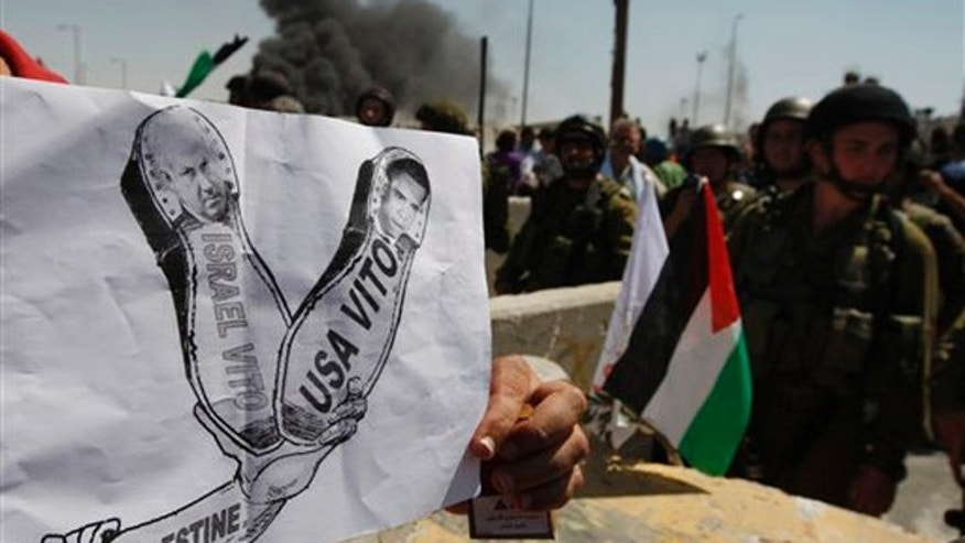 September 17: A Palestinian holds a mock poster with the image of Israeli Prime Minister Benjamin Netanyahu and U.S. President Barack Obama during a demonstration demanding the recognition of a Palestinian state, in the Qalandia checkpoint between the West Bank city of Ramallah and Jerusalem.