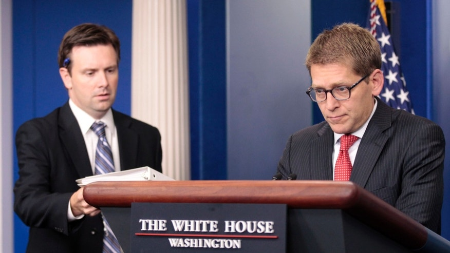 Wednesday: Principal Deputy Press Secretary Josh Earnest, left, hands off the briefing book to White House Press Secretary Jay Carney during the daily news briefing at the White House.