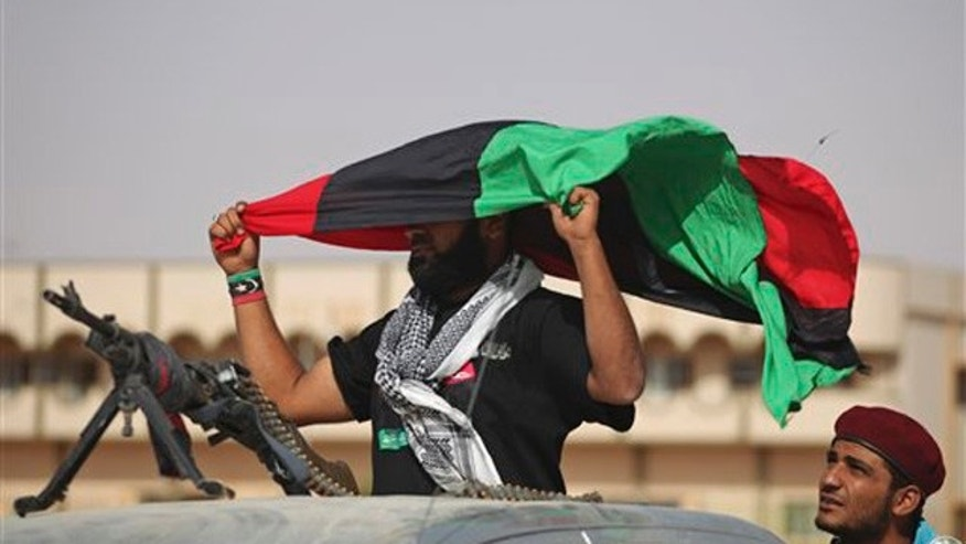 A former rebel fighter holds a pre-Gadhafi's flag at the northern gate of Bani Walid, Libya, Monday, Sept. 19, 2011.
