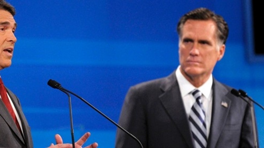 Republican presidential candidate former Massachusetts Gov. Mitt Romney, right, listens as Texas Gov. Rick Perry makes a statement during a debate Thursday, Sept. 22, 2011, in Orlando, Fla. (AP Photo/Phelan M. Ebenhack, Pool)