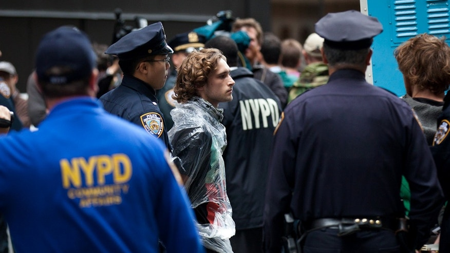 A demonstrator affiliated with Occupy Wall Street protests is arrested during a march near the financial district's Zucotti park, Monday, Oct. 12, 2011, in New York as the protest entered its fourth week.