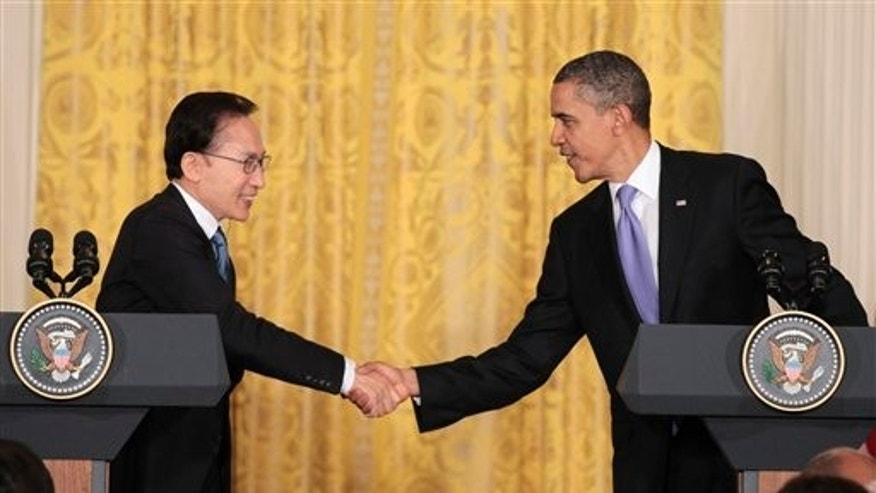 October 13: President Barack Obama and South Korean President Lee Myung-bak shake hands during their joint news conference in the East Room at the White House in Washington, D.C.
