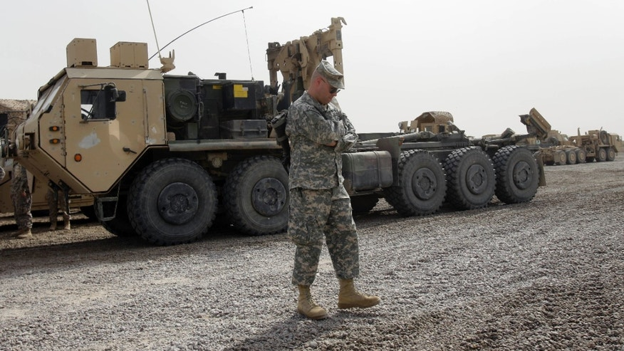 A U.S. Army soldier stands by military armored vehicles ready to be shipped out of Iraq at a staging yard at Camp Victory that is set to close in Baghdad, Iraq, Saturday, Oct. 15, 2011.