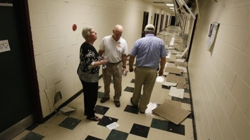 Aug. 23: Louisa County school superintendent Deborah Pettit, left, County of Louisa Green Spring District Supervisor Richard Havasy, and school board member Brian Huffman survey the damage to Louis County High school after the 5.8 magnitude earthquake in Mineral, Va.