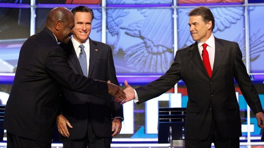 Oct. 18, 2011: Republican presidential candidates Herman Cain, left, shakes hands with Texas Gov. Rick Perry as former Massachusetts Gov. Mitt Romney looks on before a Republican presidential debate in Las Vegas.