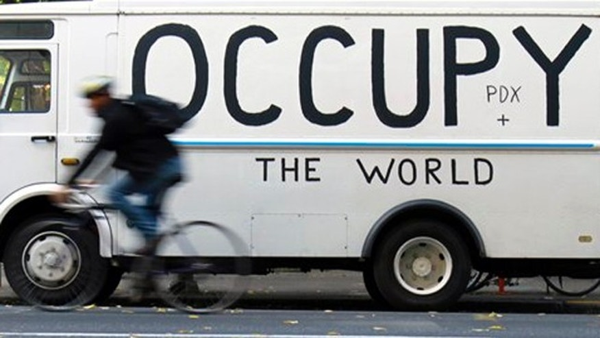 Oct. 18, 2011: A bicyclist rides past a truck and sign at the Occupy Portland camp in downtown Portland, Ore.