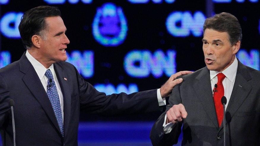 Republican presidential candidate former Massachusetts Gov. Mitt Romney, left, and Texas Gov. Rick Perry speak during a Republican presidential debate Tuesday, Oct. 18, 2011, in Las Vegas.  (AP Photo/Chris Carlson)