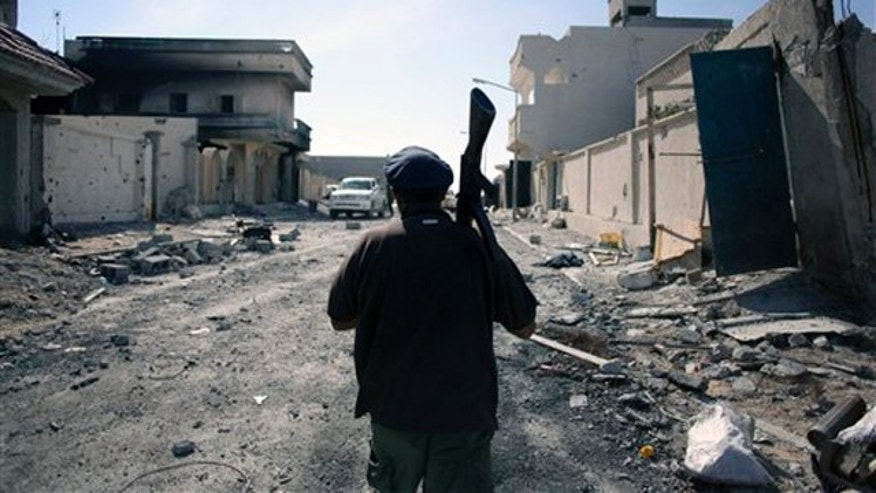 Oct. 20, 2011: A revolutionary fighter walks in the captured town of Sirte, Libya.