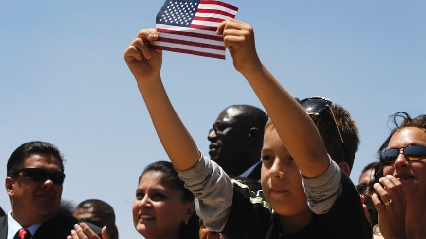 File Photo: May 2011 - A boy shows off an American flag while listening to President Barack Obama speak about immigration in Chamizal National Park in El Paso, Texas.  (Photo AP/Charles Dharapak)