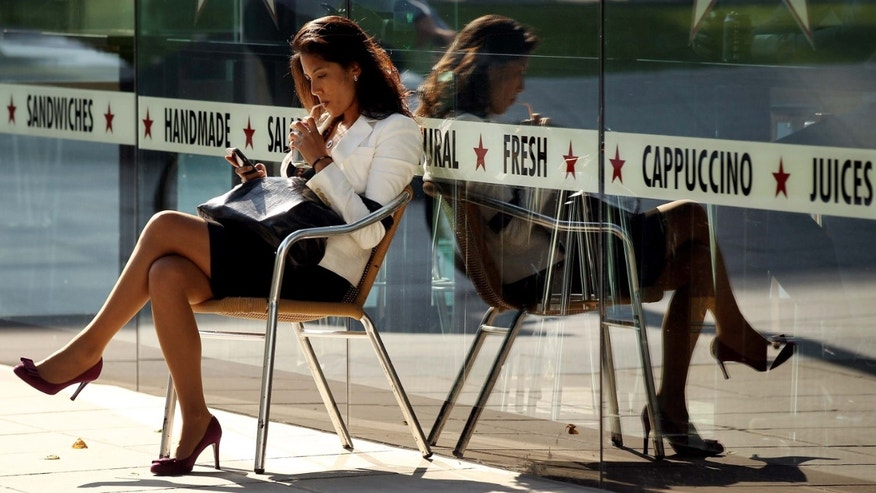 LONDON, ENGLAND - AUGUST 16:  A woman uses her mobile phone as she relaxes in the sunshine outside a cafe on August 16, 2010 in London, England. Many areas of the UK continue to experience unseasonably unsettled weather with forecasters predicting little improvement for the rest of August.  (Photo by Oli Scarff/Getty Images)