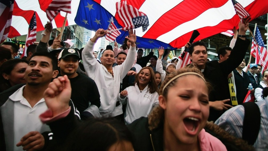 FILE - In this May 1, 2006 file photo, participants in an immigration rights rally walk under a giant American flag during a march through downtown Chicago. Figures released by the U.S. Census Bureau Tuesday, Feb. 15, 2011, show that while Illinois' populations of both whites and blacks decreased, the population of people who identified themselves as Hispanic grew at a sharp 32.5 percent rate. (AP Photo/M. Spencer Green, File)