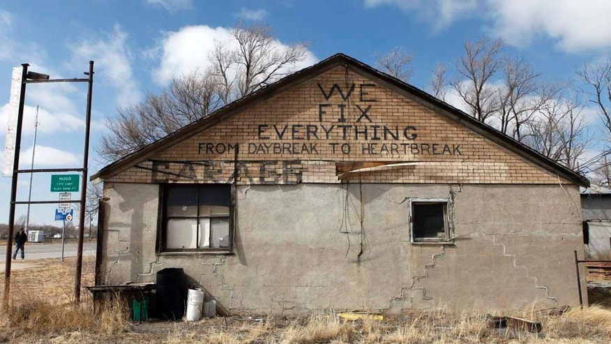 This photo taken in Hugo, Colo., on Thursday, Feb. 24, 2011, shows  a sign advertising to fix anything, including a broken heart, on the side of building that was once a garage on Main Street. Hugo, a tiny agricultural outpost is losing itself to lack of employment. (AP Photo/Ed Andrieski)