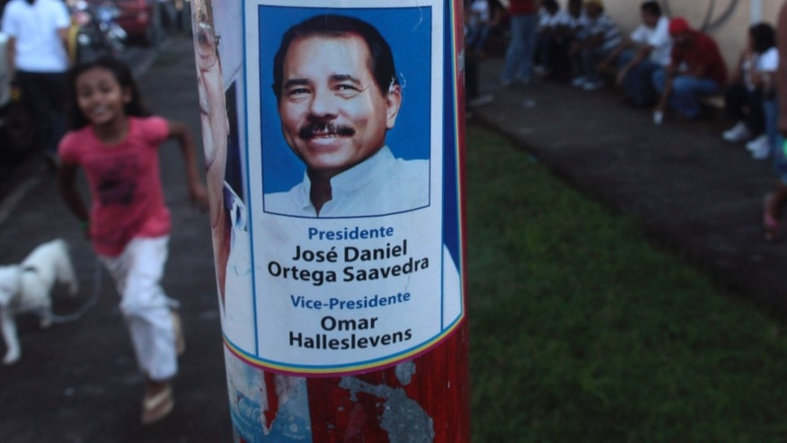 A campaign poster of Nicaragua's President Daniel Ortega is displayed on a  light pole in front of a polling station during general elections in Managua, Nicaragua, Sunday Nov. 6, 2011.  The one-time Sandinista revolutionary and and presidential candidate for the ruling Sandinista National Liberation Front, FSLN, appears headed for a third term victory Sunday in an election that Ortega's critics say could be the prelude to a presidency for life. (AP Photo/Esteban Felix)