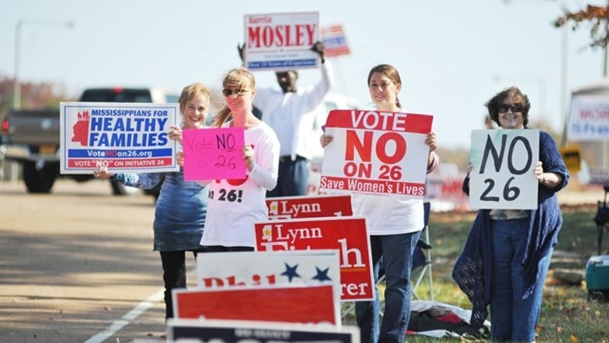 November 8, 2011: From the left, Ann Fisher-Wirth, Carley Dunavant, Jill Stevens, and Dicki King hold signs against Amendment 26 outside the polls at the Oxford Conference Center in Oxford, Miss.