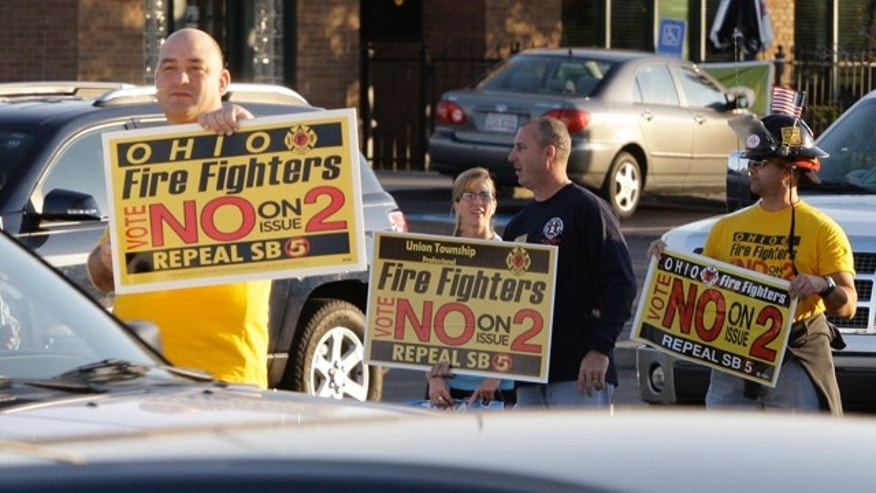 Nov. 7, 2011: A group of firefighters in Cincinnati urge passing motorists to vote no on Issue Two in Tuesday's election. Issue Two was rejected in the vote.