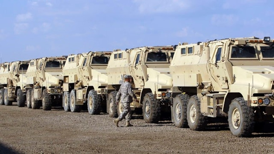 U.S. army soldiers walks past military armored vehicles are ready to be shipped out of Iraq at Camp Victory Complex that is set to close in Baghdad, Iraq, Monday, Nov. 7, 2011. (AP Photo/Khalid Mohammed)