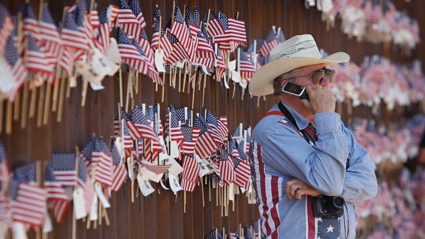 David Walker, an Arizona rancher, speaks before a decorated streach of border fence in Hereford, Arizona. (AP/Matt York)