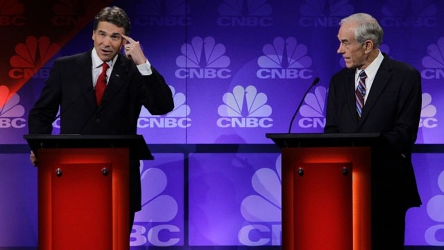 Republican presidential candidate Texas Gov. Rick Perry points his head as he speaks during a Republican Presidential Debate at Oakland University in Auburn Hills, Mich., Wednesday, Nov. 9, 2011.  At right is Rep. Ron Paul, R-Texas. (AP Photo/Paul Sancya)