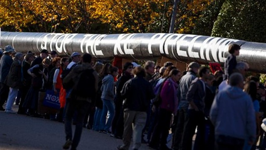 Nov. 6, 2011: Demonstrators march with a replica of a pipeline during a protest against the Keystone XL tar sands oil pipeline outside the White House.