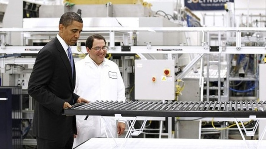 May 26, 2010: President Obama lifts a solar panel as he tours a Solyndra facility in Fremont, Calif.