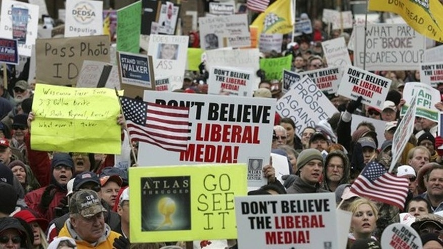April 16, 2011: People hold signs in support of the Tea Party during a Tax Day rally in Madison, Wis.