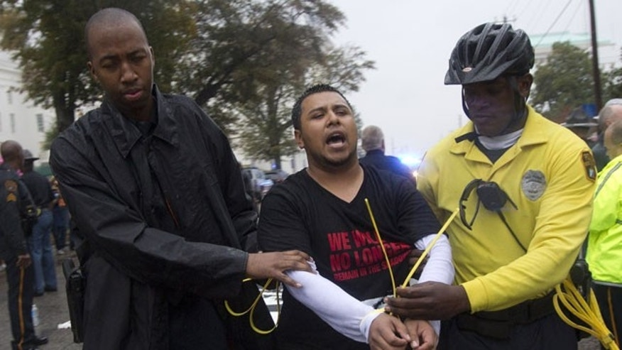 November 15, 2011: A protestor is arrested after blocking traffic outside the Alabama Statehouse during a demonstration against Alabama's immigration law in Montgomery, Ala.