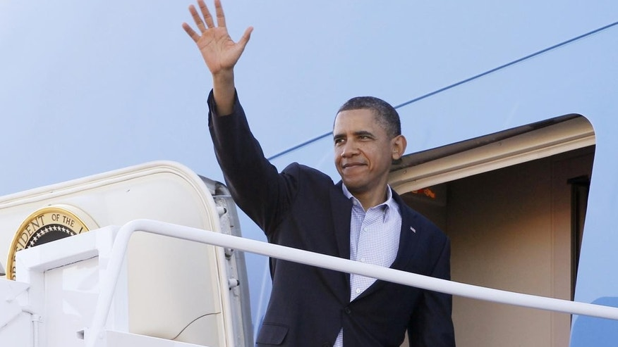 President Barack Obama waves as he boards Air Force One at Hickam Air Force Base in Honolulu, Tuesday, Nov. 15, 2011, as he travels to Canberra, Australia. (AP Photo/Charles Dharapak)