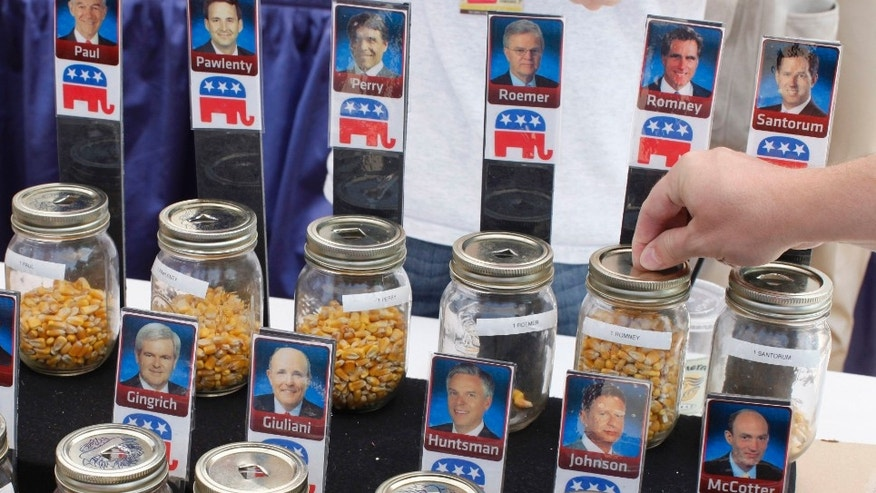 "FILE - In this Aug. 12, 2011 file photo, a visitor places a kernel of corn for Republican presidential hopeful former Massachusetts Gov. Mitt Romney during an informal ""corn poll"" at the Iowa State Fair in Des Moines, Iowa.  (AP Photo/Charles Dharapak, File)"
