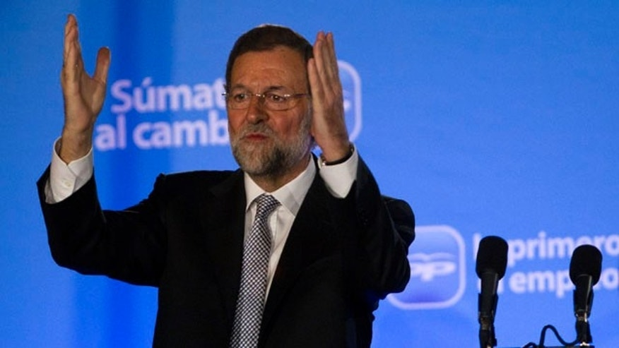 Conservative Popular Party candidate Mariano Rajoy waves next to his wife Elvira Fernandez Balboa after winning the general elections, in Madrid, Sunday Nov. 20, 2011. (AP Photo/Emilio Morenatti)