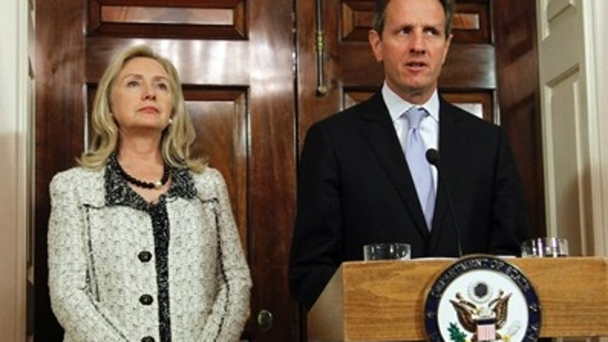 Nov. 21, 2011: Secretary of State Hillary Rodham Clinton, left, listens to Treasury Secretary Tim Geithner, speak about new sanctions the U.S. is taking to increase pressure on Iran, at the State Department in Washington.