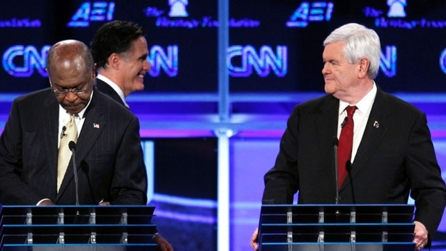 Republican presidential candidates former Massachusetts Gov. Mitt Romney walks behind Herman Cain and former House Speaker Newt Gingrich during a break at a Republican presidential debate in Washington, Tuesday, Nov. 22, 2011. (AP Photo/Evan Vucci)