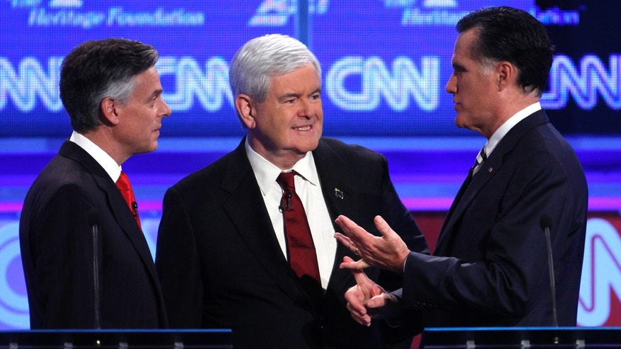 Republican presidential candidates former Utah Gov. Jon Huntsman and former House Speaker Newt Gingrich talk with former Massachusetts Gov. Mitt Romney at a Republican presidential debate in Washington, Tuesday, Nov. 22, 2011. (AP Photo/Evan Vucci)