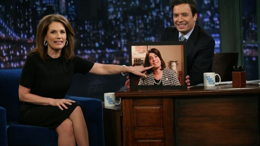 "November 22, 2011: In this image released by NBC, Republican presidential candidate Michele Bachmann, of Minnesota, left, points to a photo of host Jimmy Fallon, dressed as Bachmann, during a visit to ""Late Night with Jimmy Fallon."""