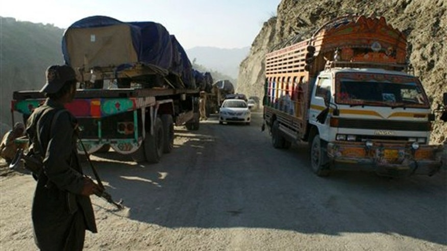 Nov. 26, 2011: A border security guard stands near Afghanistan-bound NATO trucks at the Pakistani border town of Torkham.