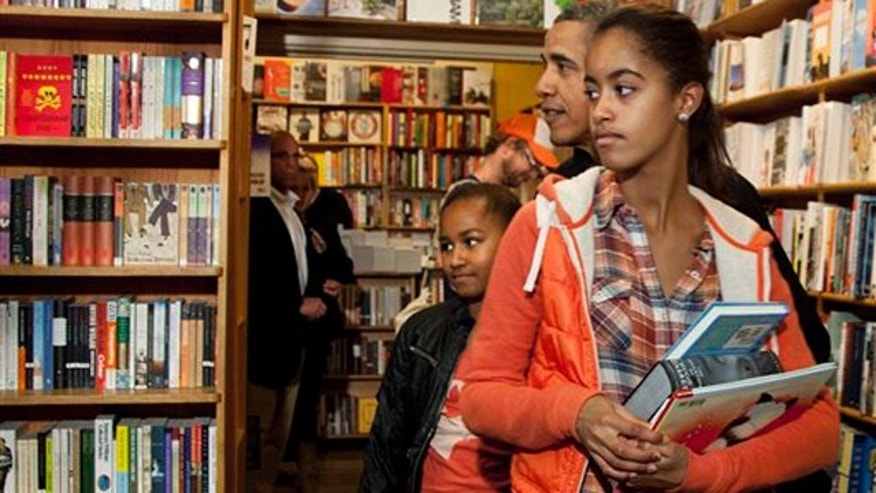 Nov. 26, 2011: President Obama visits Kramerbooks in Washington, D.C., while shopping with his daughters Malia, foreground, and Sasha.