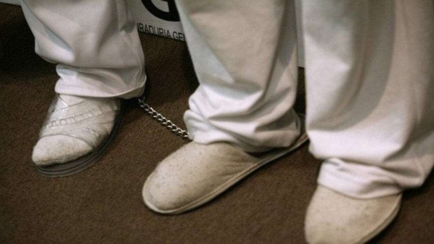 Oct. 19, 2011: Human-trafficking suspects are chained to each other's ankles while being presented to the media in Mexico City.