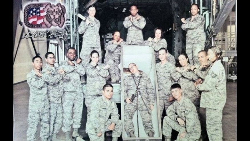 Air Force officials say they are investigating this photo of 15 airmen posing with another airman pretending to be dead and lying in an open casket with a noose around his neck.