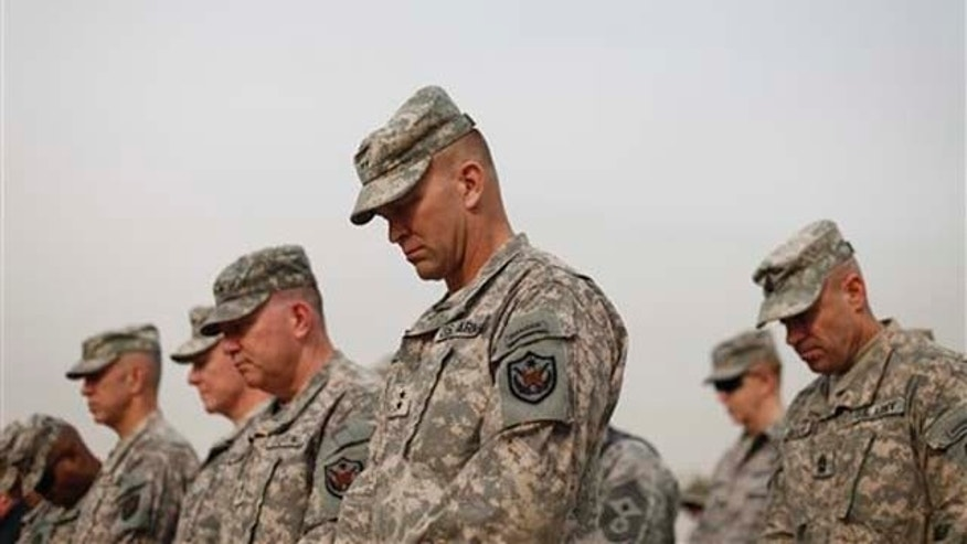 DEC. 15, 2011: Military personnel lower their heads during ceremonies of the encasing of the US Forces Iraq colors, in Baghdad, Iraq, on Thursday. The ceremonies mark the official end of the US military mission in Iraq.