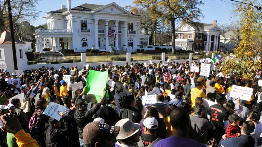 Protest against Alabama's House Bill 56 in front of the Governor's Mansion on Saturday, Dec. 17, 2011, in Montgomery, Ala.. (AP Photo/Montgomery Advertiser, Lloyd Gallman) NO SALES