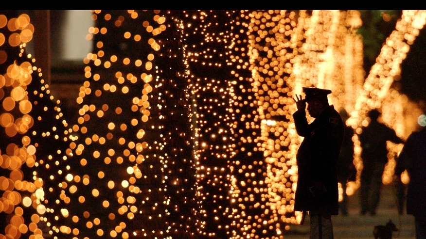 A police agent fixes his hat near trees decorated with Christmas lights in Reforma Avenue, Tuesday, Dec. 21, 2004 in Mexico City. (AP Photo/Jaime Puebla)