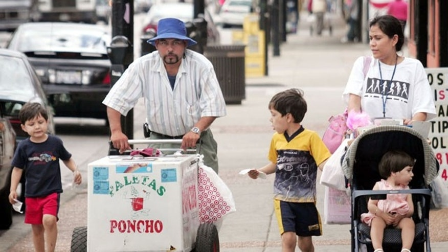 CHICAGO - JUNE 14: Residents walk past a paleta vendor along 26th Street in the predominantly Mexican Little Village neighborhood June 14, 2005 in Chicago, Illinois. According to the U.S. census Hispanics accounted for approximately half of the national population growth between July 1, 2003 and July 1, 2004 now accounting for one-seventh of the population.  (Photo by Scott Olson/Getty Images)
