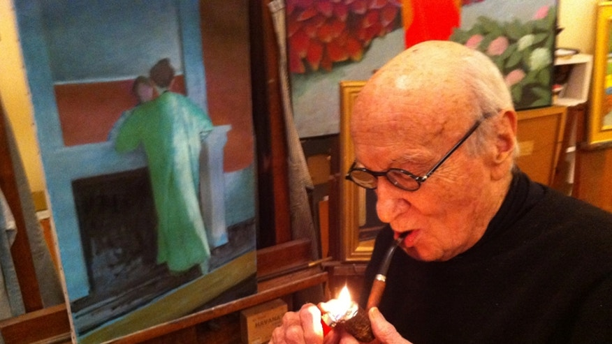Painter Aaron Shikler lights his pipe in front of a portrait of his wife.