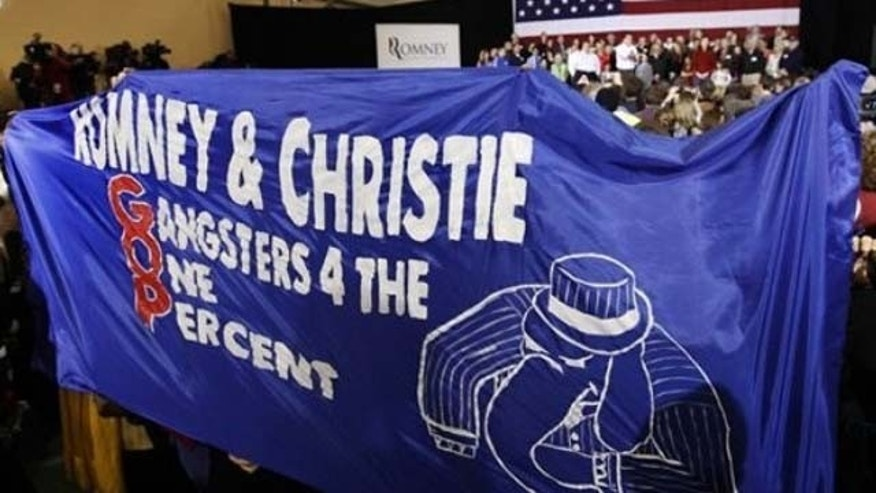 January 8, 2012: Protesters unfurl a sign as Republican presidential candidate, former Massachusetts Gov. Mitt Romney, accompanied by New Jersey Gov. Chris Christie, speaks at a campaign rally in Exeter, N.H.