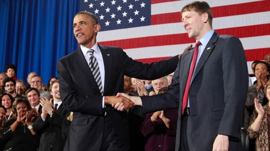 Jan. 4, 2012: President Obama shakes hands with Richard Cordray before speaking about the economy at Shaker Heights High School in Ohio.