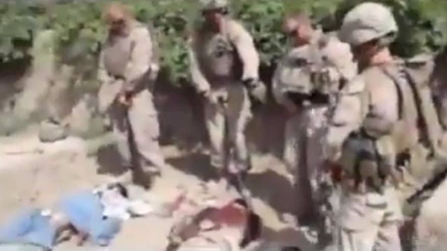 This image taken from a video posted on YouTube appears to show four Marines as they prepare to urinate on corpses.