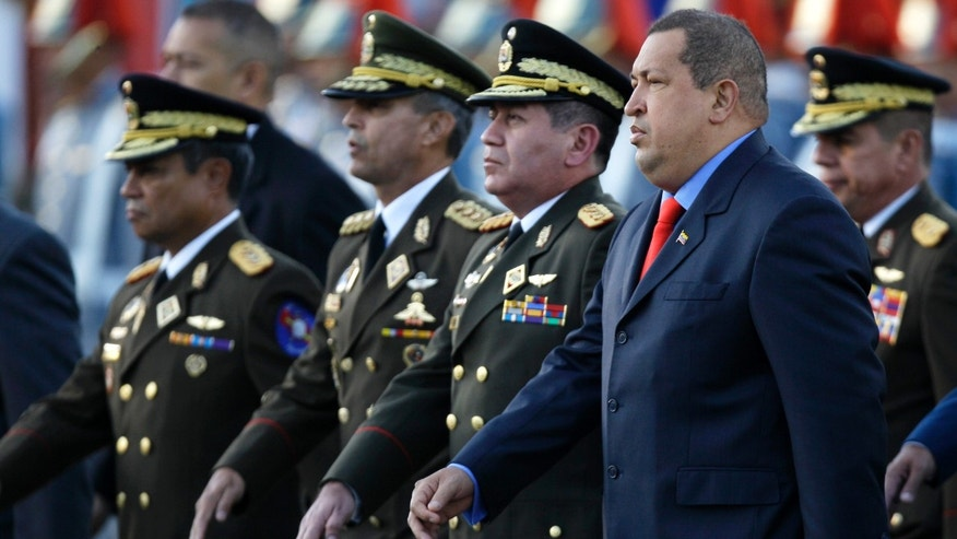 Venezuela's President Hugo Chavez, right, and incoming Defense Minster Gen. Henry Rangel Silva, second from right, arrives to attend Rangel Silva's  swearing-in ceremony at Fort Tiuna military base in Caracas, Venezuela, Tuesday, Jan. 17, 2012. (AP Photo/Fernando Llano)